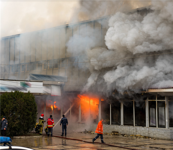 Firefighters putting out a fire in a big building